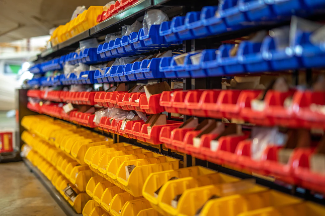 rows of red, yellow, and blue organizers holding small parts and products