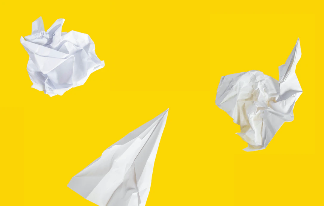 crumpled pieces of paper on a bright yellow background